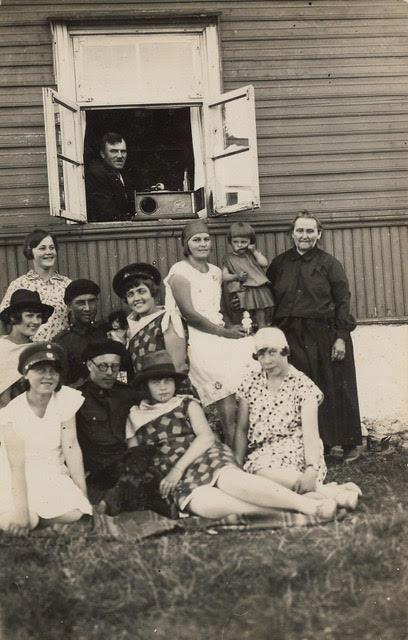 Põhjakülas 1929: aknal Johannes Pilk, akna all naine Anna koos ema Ann'i ja tütar Helvega, paremal istub Olga Viliberg (Bertelson), mees esireas Oskar Markus